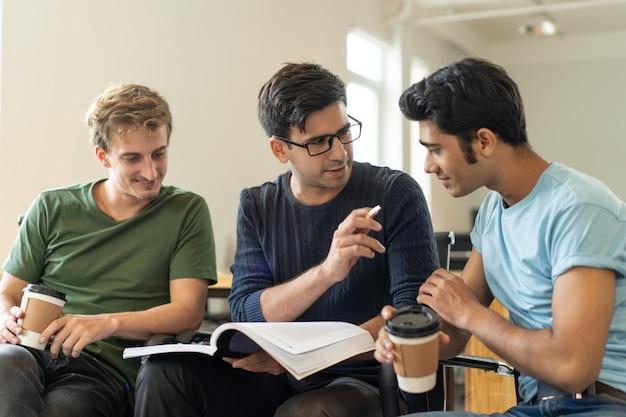 Confident hispanic guy explaining task to indian student