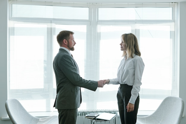 Confident hr manager shaking hand of young successful applicant while congratulating her on beginning of new career after interview