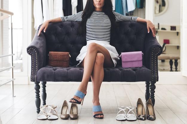 彼女の選択に自信を持っています。靴屋のソファに座って膝で足を組んでいる美しい若い女性の一部