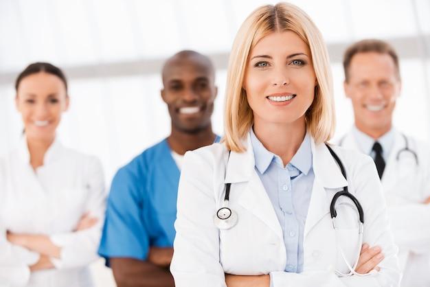 彼女のチームに自信を持っています。彼女の同僚がバックグラウンドで彼女の後ろに立っている間、腕を組んで笑顔を保つ美しい女性医師