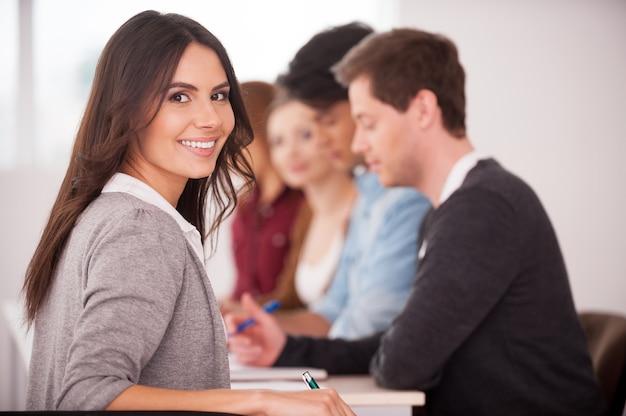 Уверена в своей команде. вид сзади красивой молодой женщины, глядя через плечо и улыбаясь, сидя вместе за столом с другими людьми