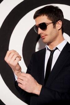 自信がある。黒と白の背景に立っている間彼のシャツの袖口を調整する正装とサングラスのハンサムな若い男