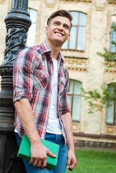 彼の明るい未来に自信を持っています。本を持って大学の建物に立ち向かい笑顔で見上げるハンサムな男子学生のローアングルビュー
