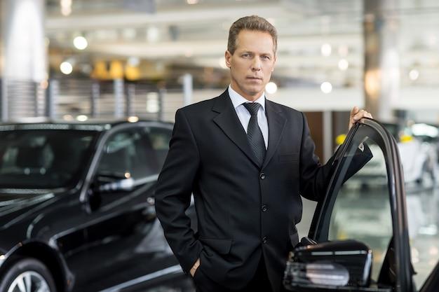 자신의 선택을 확신합니다. 열린된 차 문에 손을 잡고 카메라를 보고 formalwear에서 자신감 회색 머리 남자