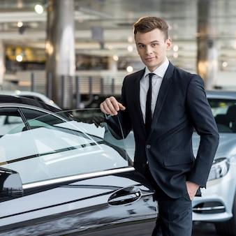 자신의 선택을 확신합니다. 차 문에 기대어 차 대리점에 서있는 동안 카메라를보고 formalwear에서 자신감이 젊은 남자
