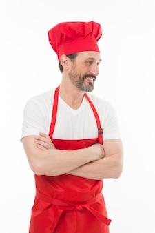 彼の料理のスキルに自信があります。よだれかけのエプロンを身に着けているひげと口ひげを生やした上級料理人。赤い調理エプロンで成熟したチーフクック。シェフの帽子とエプロンでひげを生やした成熟した男。家庭料理。