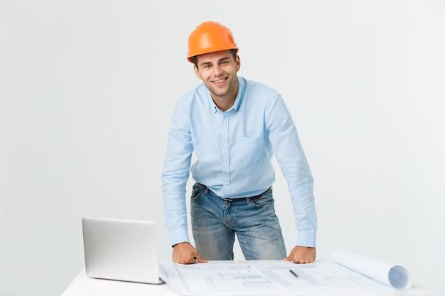 彼の新しいプロジェクトに自信を持っています。ラップトップで作業し、彼のオフィスに立っている間笑顔でカメラを見ている若いエンジニアと建築家の男。