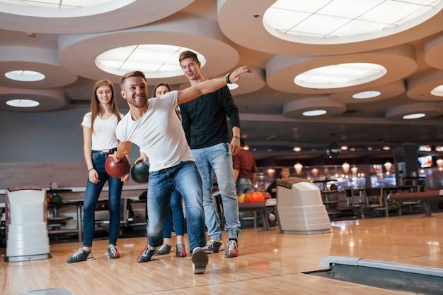 Уверен в своей силе. молодые веселые друзья веселятся в боулинг-клубе на выходных