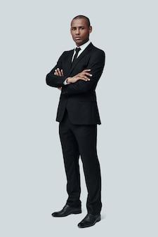 자신의 스타일에 자신감. 회색 배경에 서서 카메라를 바라보는 정장 차림의 잘생긴 젊은 아프리카 남자의 전체 길이