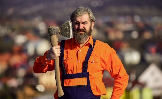 자신의 일에 자신감이 있습니다. 건설 및 건설. 숙련된 건축가가 수리 및 수리합니다. 엔지니어 경력. 제복을 입은 수염난 남자. 성숙한 남자 빌더는 도끼를 사용합니다. 도끼 도구로 작업하는 전문 수리공.