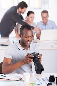 자신의 일에 자신감이 있습니다. 세 사람이 배경 작업을 하는 동안 카메라를 들고 웃고 있는 자신감 있는 젊은 아프리카 남자