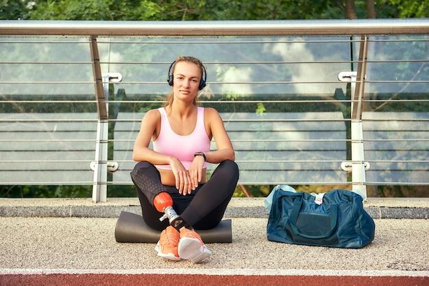 Уверенный в себе портрет молодой женщины в спортивной одежде и наушниках с протезом ноги