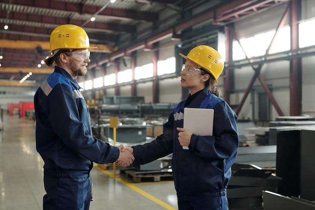 合意に達した後、ワークショップで握手をする作業服と保護ゴーグルの自信を持って産業の同僚