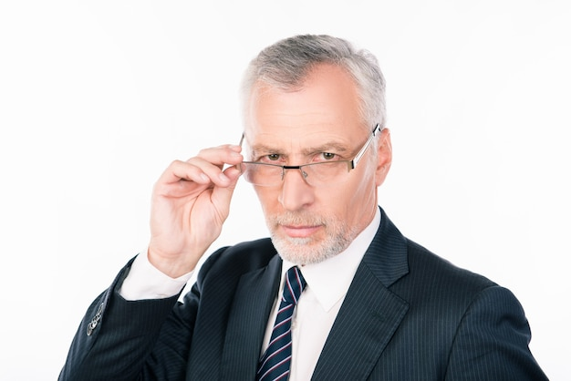 Уверенно умный старик в деловом костюме с очками