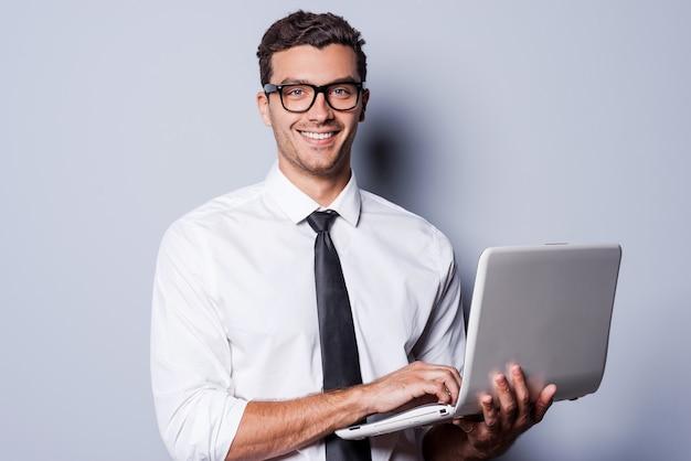 자신감 있는 it 전문가. 셔츠와 넥타이를 매고 노트북 작업을 하고 회색 배경에 서서 웃고 있는 잘생긴 청년