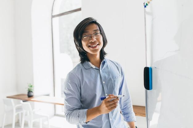 ホワイトボードの近くに立って、マーカーを保持している流行のメガネで自信を持って日本人学生