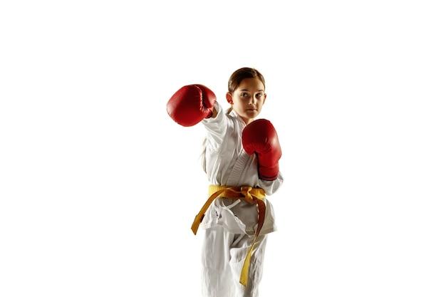 近接格闘術、武道を練習する着物の自信のあるジュニア。白い壁に黄色いベルトのトレーニングをしている若い女性の戦闘機。健康的なライフスタイル、スポーツ、アクションの概念。