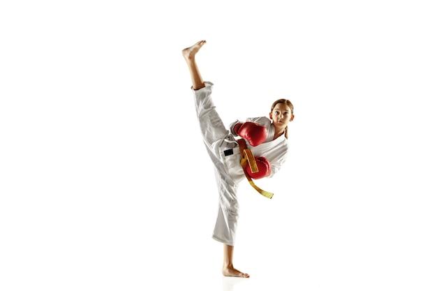 Уверенный юноша в кимоно, практикует рукопашный бой, боевые искусства. молодой женский боец с тренировкой желтого пояса на белой стене. концепция здорового образа жизни, спорта, действий.