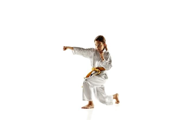 近接格闘術、武道を練習する着物の自信のあるジュニア。白い壁に黄色いベルトのトレーニングをしている若い女性の戦闘機。健康的なライフスタイル、スポーツ、アクションの概念。 Premium写真