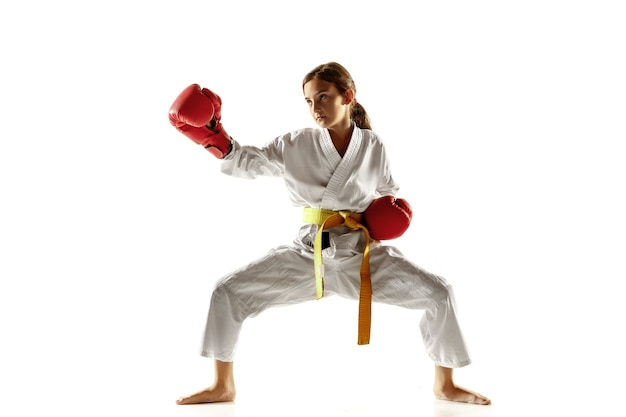 Confident junior in kimono practicing hand-to-hand combat, martial arts. young female fighter with yellow belt s training on white  wall. concept of healthy lifestyle, sport, action.