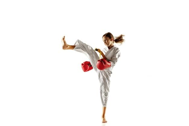 Confident junior in kimono practicing hand-to-hand combat, martial arts.