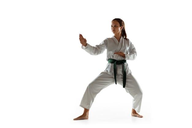 Confident junior in kimono practicing hand-to-hand combat