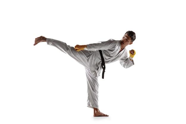 白兵戦、武道を練習する着物に自信を持っている韓国人。白い壁に隔離された黒帯の訓練を受けた若い男性の戦闘機。健康的なライフスタイル、スポーツの概念。