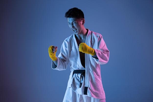 白兵戦、武道を練習する着物に自信を持っている韓国人。ネオン光の勾配壁で黒帯の訓練を受けた若い男性の戦闘機。健康的なライフスタイル、スポーツの概念。 Premium写真