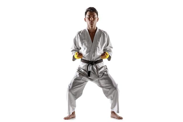 기모노 차림의 자신감 있는 한국 남자가 손으로 잡는 무술을 연습한다