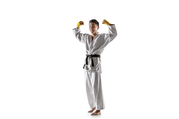 Confident korean man in kimono practicing hand-to-hand combat, martial arts. young male fighter with black belt celebrates win isolated on white wall. concept of healthy lifestyle, sport.