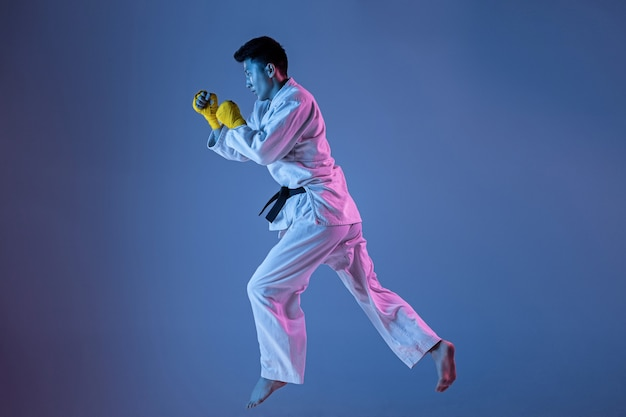 Confident korean man in kimono practicing hand-to-hand combat, martial arts. young male fighter with black belt training on gradient background in neon light. concept of healthy lifestyle, sport.