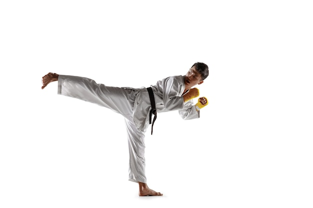 Confident korean man in kimono practicing hand-to-hand combat, martial arts. young male fighter with black belt training isolated on white studio background. concept of healthy lifestyle, sport.