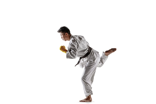 Uomo coreano sicuro in kimono che pratica combattimento corpo a corpo, arti marziali. giovane combattente maschio con formazione cintura nera isolato su bianco di sfondo per studio. concetto di stile di vita sano, sport.