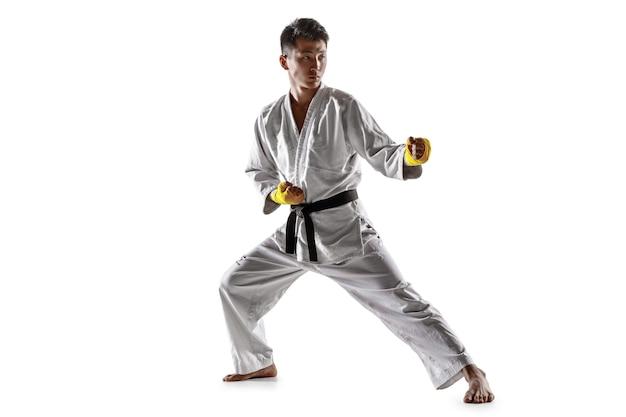 Uomo coreano sicuro in kimono che pratica combattimento corpo a corpo, arti marziali. giovane combattente maschio con addestramento della cintura nera isolato sulla parete bianca. concetto di stile di vita sano, sport.