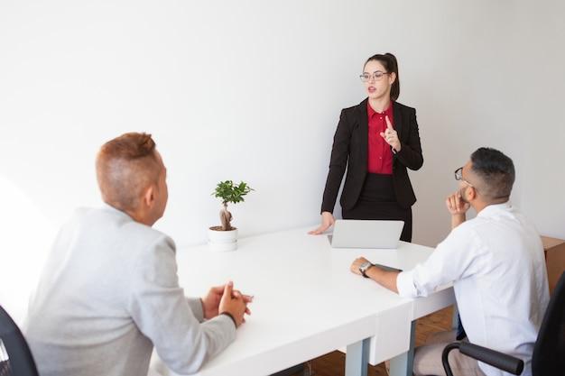 Confident lady boss conducting staff meeting