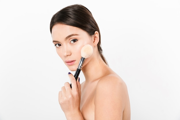 Confident lady holding makeup brush and isolated