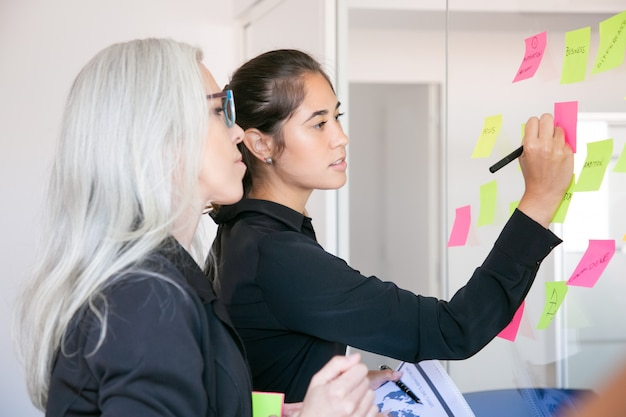 Confident latin businesswoman writing on stickers and sharing ideas for project. focused grey-haired female manager reading notes on glass wall