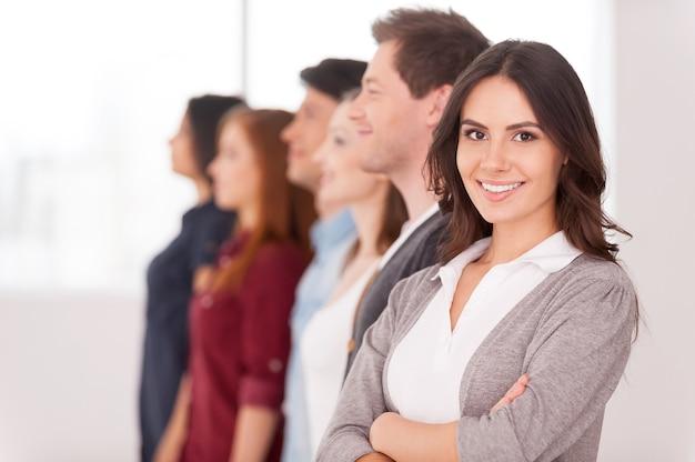 Уверенный лидер. привлекательная молодая женщина, держащая скрещенные руки и улыбаясь, в то время как группа людей, стоящих за ней в ряд