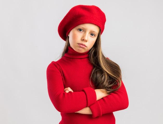 Fiduciosa bambina bionda che indossa un berretto rosso che tiene le braccia incrociate guardando la telecamera isolata sul muro bianco con spazio di copia
