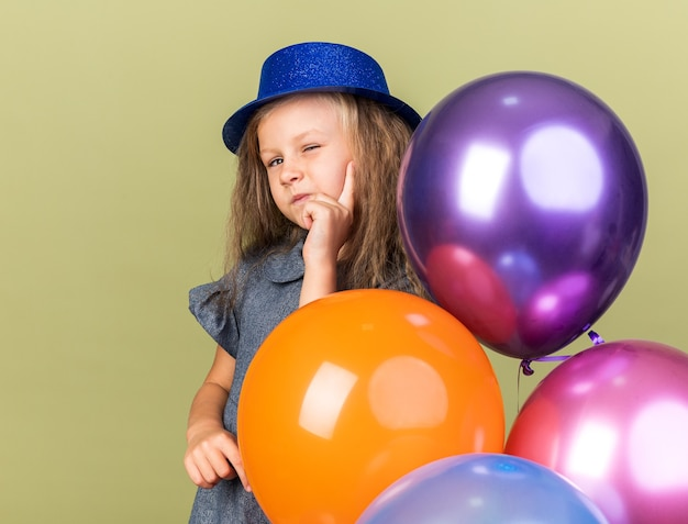Confident little blonde girl with blue party hat blinks her eye holding helium balloons isolated on olive green wall with copy space