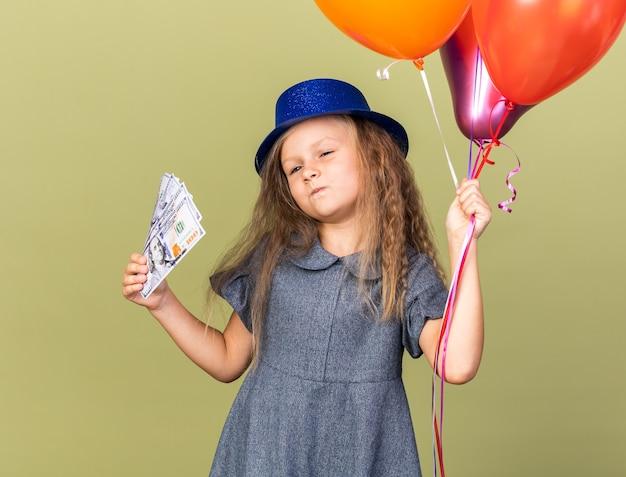 Fiduciosa bambina bionda con cappello da festa blu che tiene palloncini di elio e denaro isolato su parete verde oliva con spazio di copia