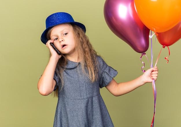 Fiduciosa bambina bionda con cappello da festa blu che tiene palloncini di elio e parla al telefono isolato su parete verde oliva con spazio di copia