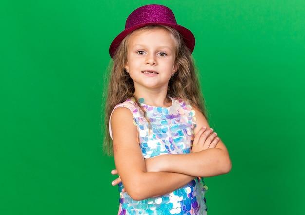 コピースペースと緑の壁に分離された腕を組んで立っている紫色のパーティハットを持つ自信のある小さなブロンドの女の子