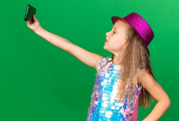 Confident little blonde girl with purple party hat taking selfie on phone isolated on green wall with copy space