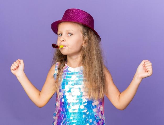 Уверенная в себе маленькая блондинка в фиолетовой шляпе, дует в свисток и держит кулаки на фиолетовой стене с копией пространства