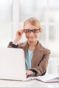Уверенная маленькая бизнес-леди. милая маленькая девочка в строгой одежде поправляет очки и улыбается, сидя за столом и используя ноутбук