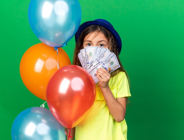 Confident little caucasian girl with blue party hat holding helium balloons and money isolated on green wall with copy space
