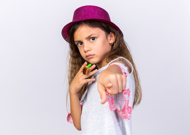 Confident little caucasian girl with purple party hat holding party whistle and pointing isolated on white wall with copy space