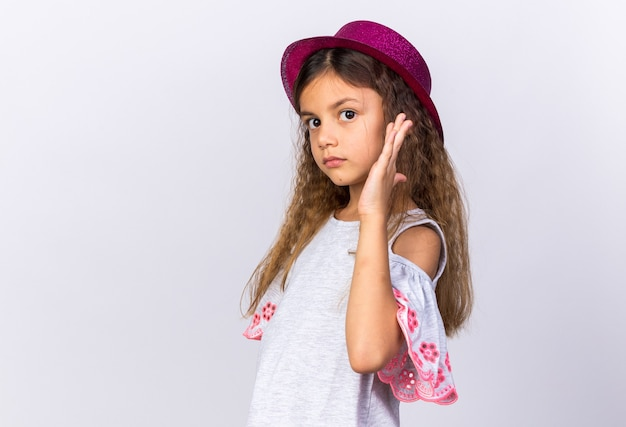 Confident little caucasian girl with purple party hat standing with raised hand isolated on white wall with copy space