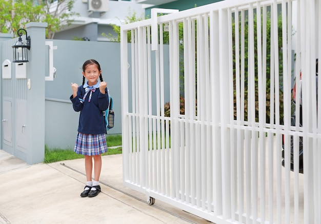 Уверенная маленькая девочка в школьной форме детского сада поднимает руки вверх перед уходом из дома